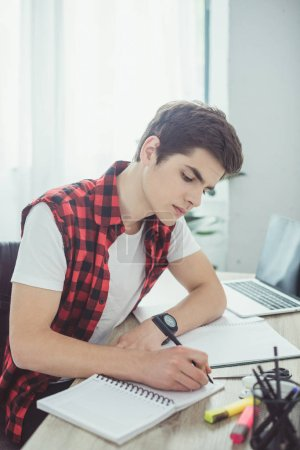 young male student writing homework at table
