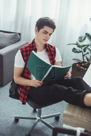 Photo for Male student reading textbook at table at home - Royalty Free Image