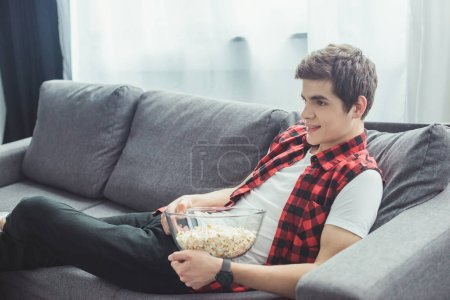 teenager with popcorn watching tv and sitting on sofa at home