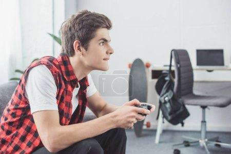 Foto de Muchacho adolescente jugando video juego con gamepad en casa - Imagen libre de derechos