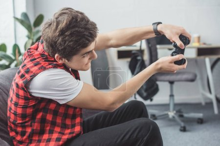 excited teen gamer playing video game with joystick at home