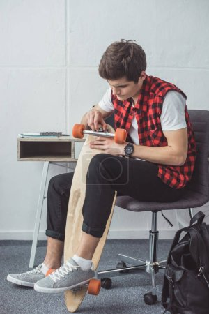 handsome teen skater fixing his longboard at home