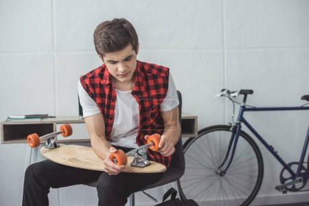 young skateboarder repairing his longboard at home
