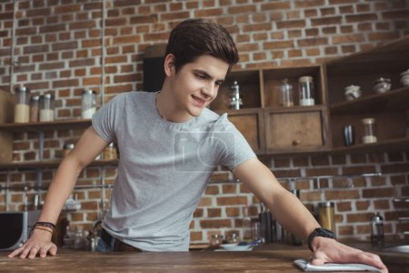 Photo for Handsome teen boy cleaning table with rag in kitchen - Royalty Free Image