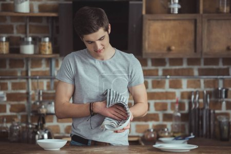 young male teenager cleaning dinnerware with towel on kitchen