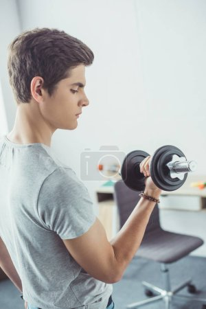 young teenager exercising with dumbbell at home
