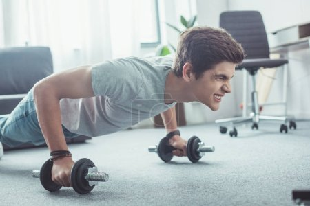 young boy doing push ups with dumbbells at home