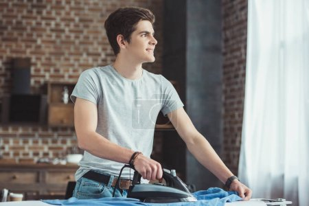 dreamy caucasian teenager ironing blue shirt at home
