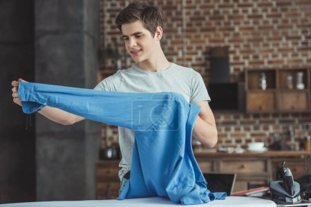 teenager holding blue shirt near ironing board with iron