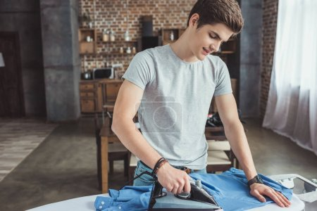 handsome teenager ironing blue shirt with iron