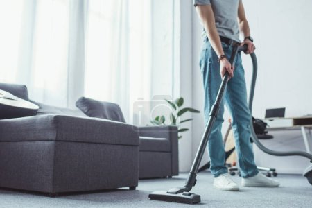 cropped view of young man cleaning floor with vacuum cleaner