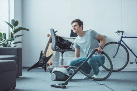 smiling teenager cleaning floor with vacuum cleaner in living room