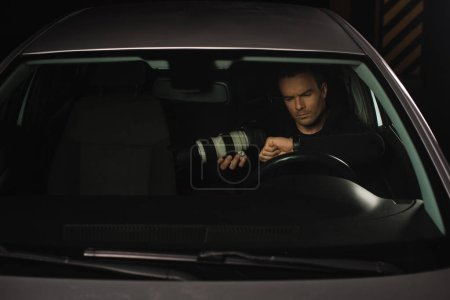paparazzi doing surveillance with camera and looking at wristwatch in car