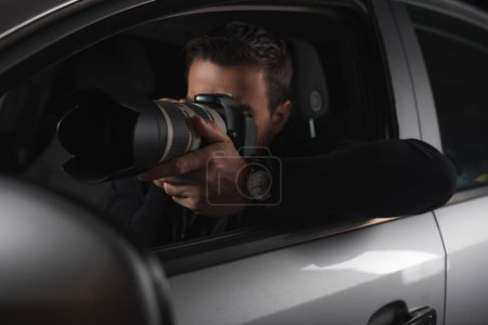 paparazzi doing surveillance by camera with lens from his car