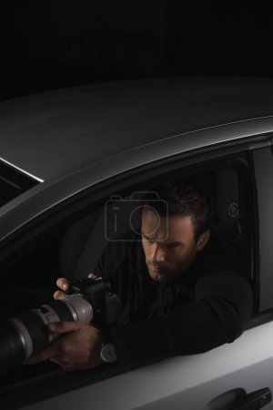 high angle view of paparazzi doing surveillance by camera from his car