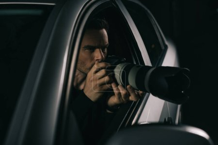 focused paparazzi doing surveillance by camera from his car