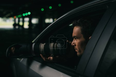 side view of male paparazzi doing surveillance with camera from his car