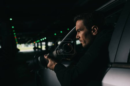 side view of male paparazzi doing surveillance by camera from his car