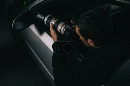 back view of undercover agent doing surveillance by camera with object glass from his car