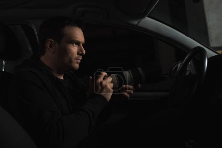 side view of male paparazzi spying by camera with lens from his car