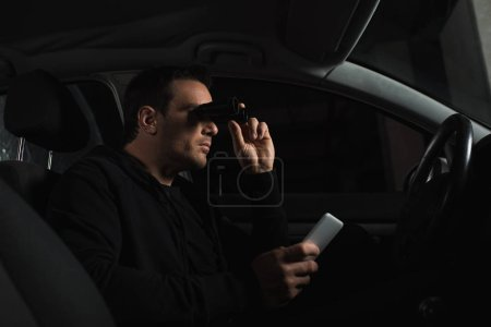 male paparazzi  with smartphone in hand doing surveillance by binoculars from car