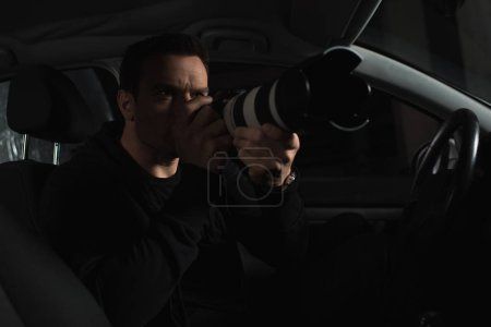 male paparazzi doing surveillance by camera from his car