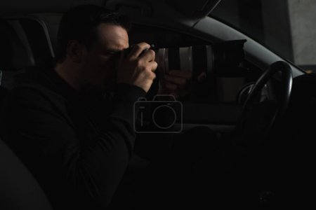 side view of concentrated man doing surveillance by camera with object glass from his car
