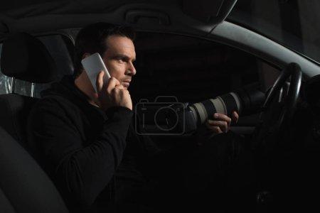 Photo pour Detceitve privé mâle parler sur smartphone et faire la surveillance par caméra dans sa voiture - image libre de droit