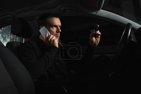 concentrated undercover male agent doing surveillance by binoculars and talking on smartphone in car