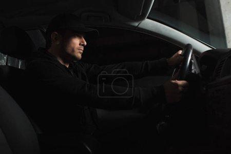 Photo pour Vue latérale du concentré paparazzi mâle faisant la surveillance et la conduite de voiture - image libre de droit