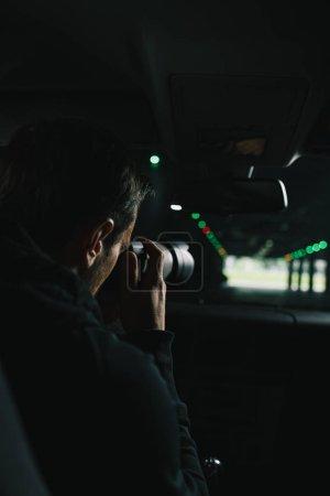 Photo pour Vue arrière de l'homme faisant de la surveillance par caméra avec des objets en verre de sa voiture - image libre de droit