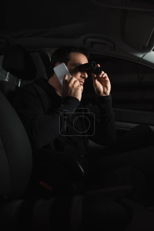 man doing surveillance by binoculars and talking on smartphone in car