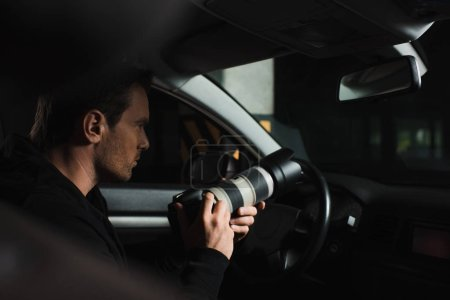 concentrated male paparazzi doing surveillance by camera with lens from his car