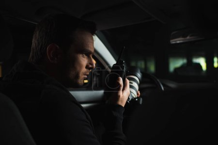 focused male paparazzi doing surveillance by camera and using talkie walkie in car