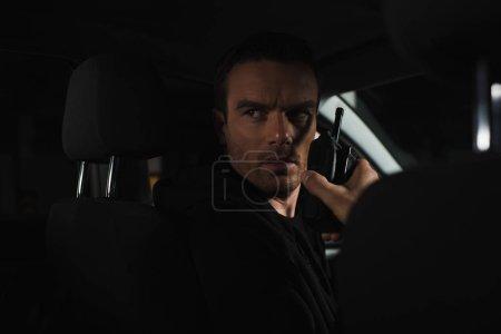 Photo pour Sérieux détective privé mâle à l'aide de talkie walkie en voiture - image libre de droit