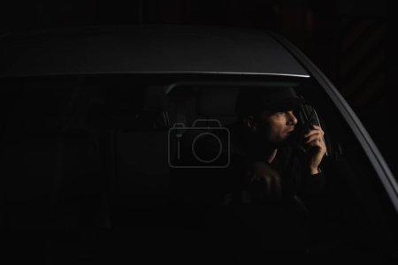 Photo pour Vue de face du détective privé mâle bouchon à l'aide de talkie walkie en voiture - image libre de droit
