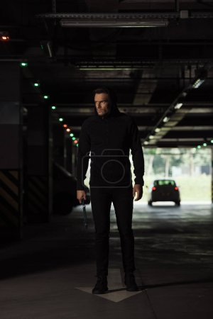 Photo for Male robber in black hoodie standing with pair of nippers - Royalty Free Image