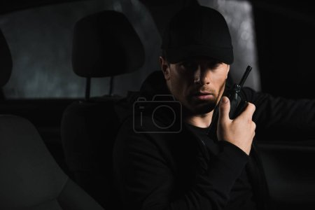 serious male private detective in cap doing surveillance and using talkie walkie in his car