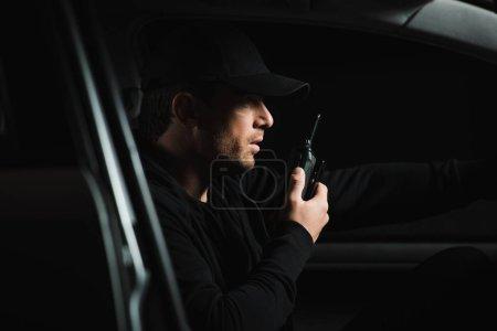 Photo pour Vue latérale du mâle paparazzi dans cap faisant la surveillance et à l'aide de talkie walkie dans sa voiture - image libre de droit