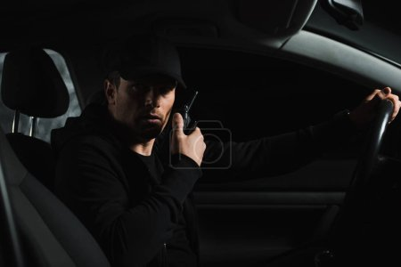 serious man in cap doing surveillance and using talkie walkie in his car