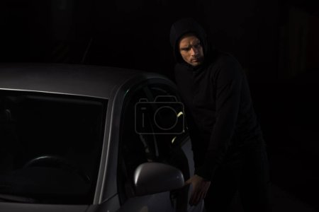 focused male thief in black hoodie intruding automobile