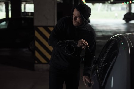 cautious male thief in black hoodie intruding car by picklock
