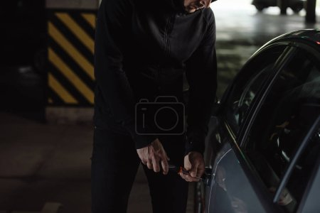 cropped shot of male robber in black hoodie intruding car by screwdriver