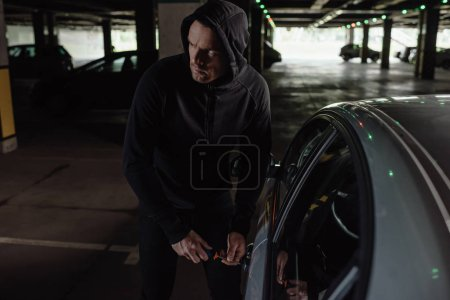 cautious male robber in black hoodie intruding car by screwdriver