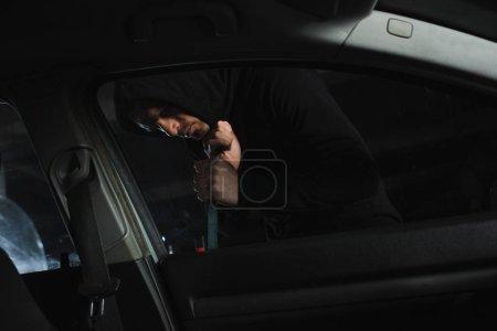 male mugger in black hoodie intruding car by crowbar