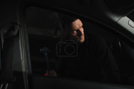 Photo for Male robber in black hoodie intruding car by pair of nippers - Royalty Free Image