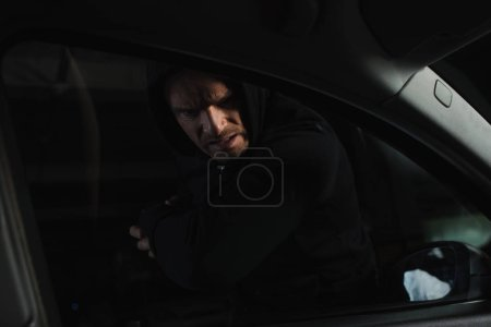 serious male robber in black hoodie breaking car window by elbow