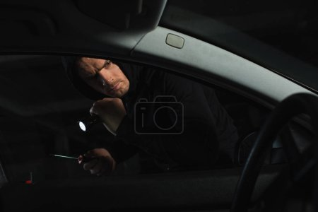 male thief in black hoodie with flashlight and screwdriver looking into car