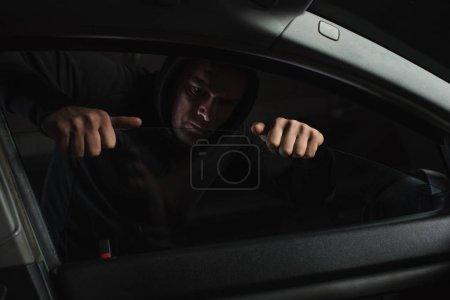 focused male robber in black hoodie intruding car