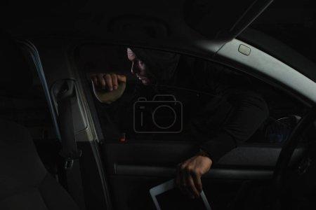 male thief in black hoodie stealing digital tablet from car
